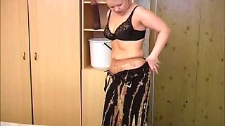 Chubby short-haired milf strips and pees in a bucket
