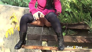 Lusty raven haired sex pot in pink coat pisses sitting on bench
