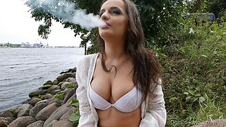 Sexy brunette in white lingerie smokes while caressing her tits