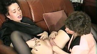 Lovely white brunette lady on the couch receives cunilingus from her friend